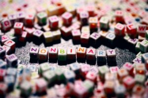 Image shows lots of small cuboid beads with coloured letters on. In the middle, the cubes are arranged to spell the word nonbinary.